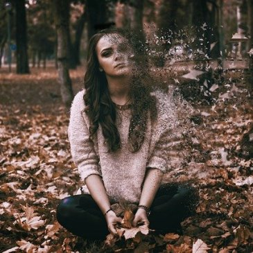woman sitting in the woods, and pieces of her are flying off like she's disintegrating