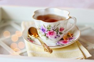 a flowered tea cup with tea in it, a golden spoon, and an impression of a fancy or high tea