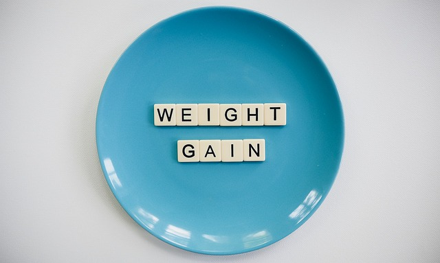 a bright blue plate with the words weight gain spelled on it in Scrabble tiles