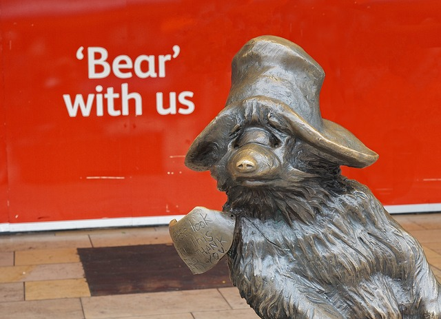 "Bronze paddington bear statue with the test ""Bear with us"""