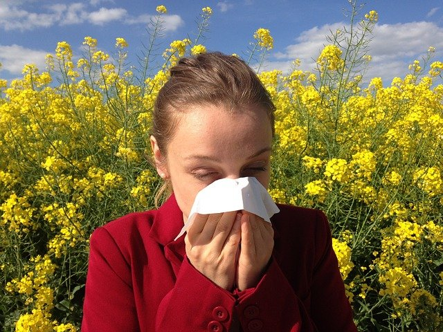 woman sneezing into a tissue in front of flowers