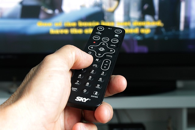 hand pointing a remote control at a television