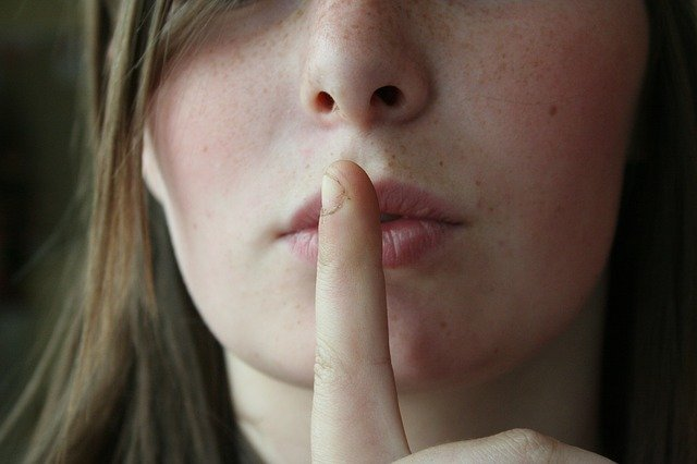 woman with her finger to her lips to indicate that silence is desired