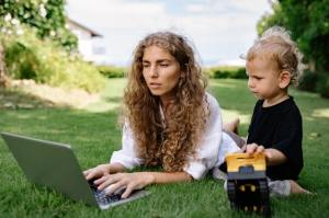woman writing lying down on her stomach with a laptop in front of her and a child next to her