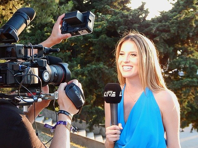 female news anchor with camera pointed at her on location